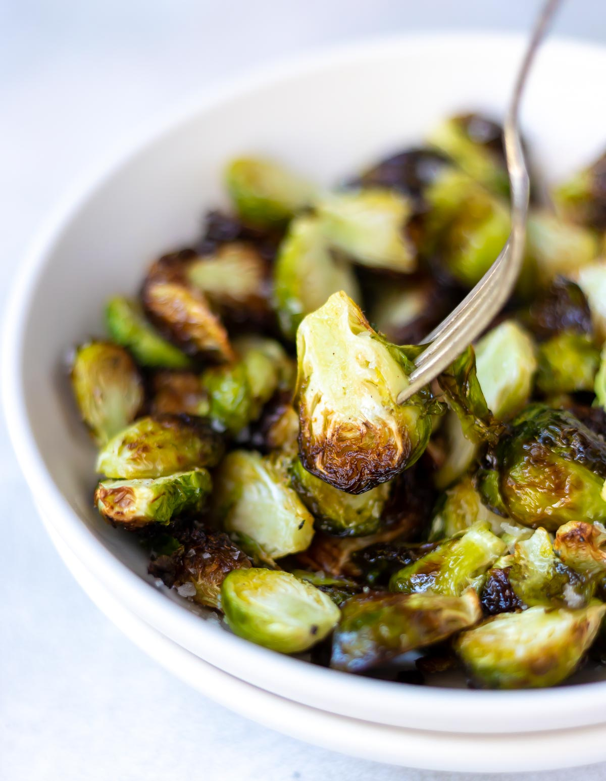 air fryer brussels sprouts in white bowl with silver fork