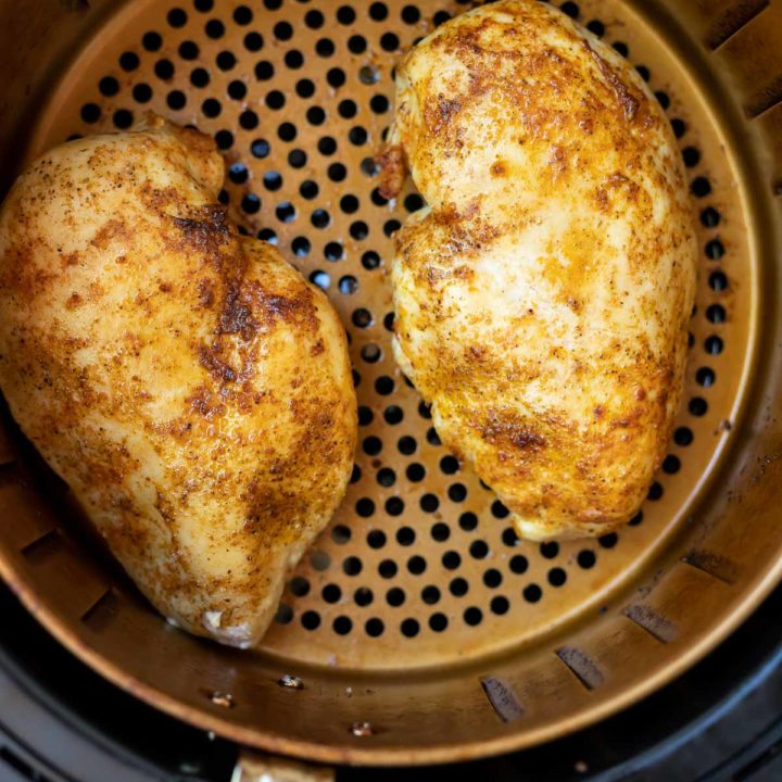 seasoned air fryer chicken breast in fryer basket