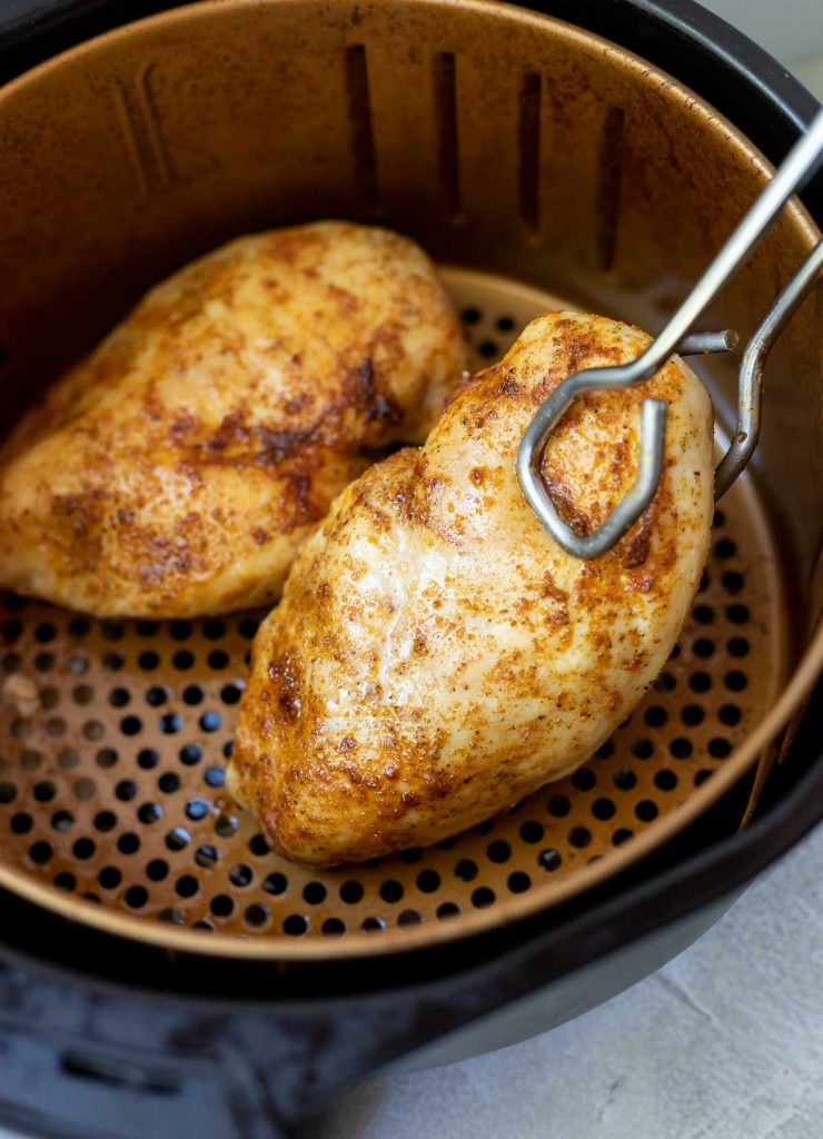 air fryer chicken breast being removed from basket with tongs