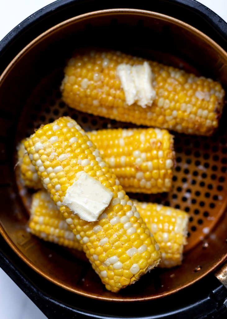 corn on the cob topped with butter in air fryer basket
