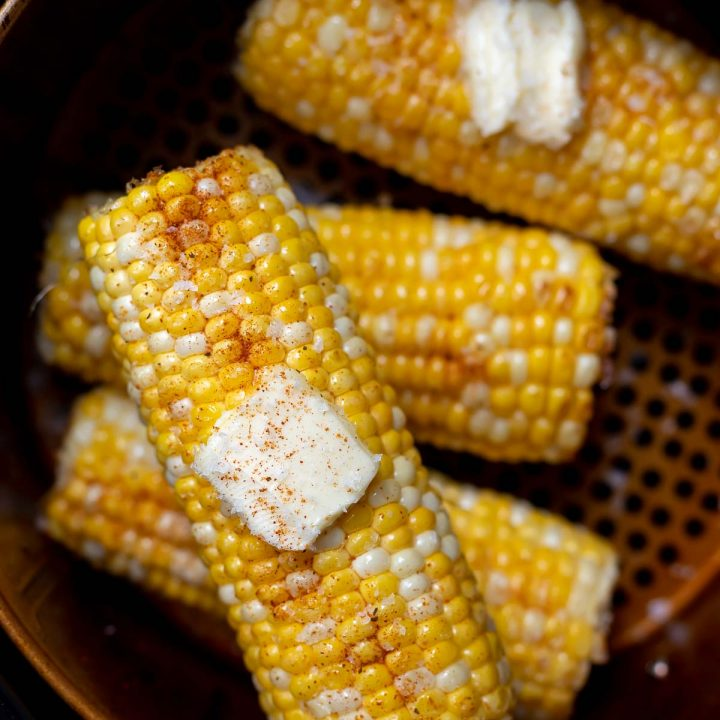 yellow corn on the cob topped with butter and spices, in air fryer basket