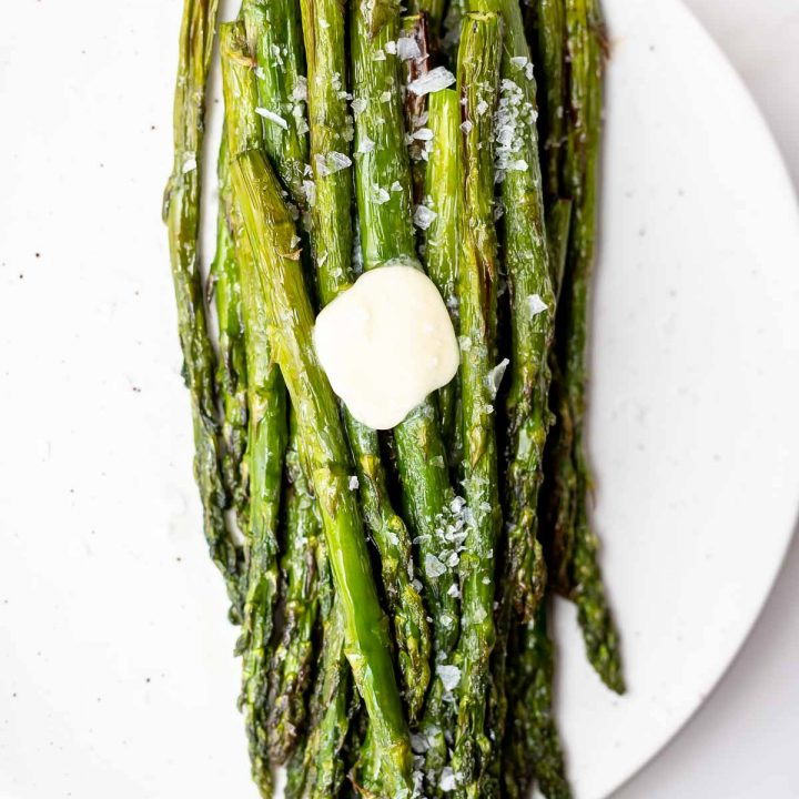 air fried asparagus on white plate, topped with salt and butter