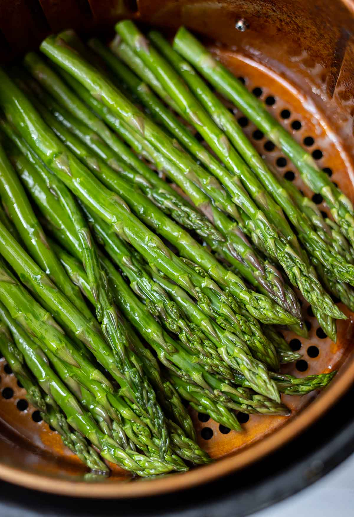 fresh raw asparagus in air fryer basket