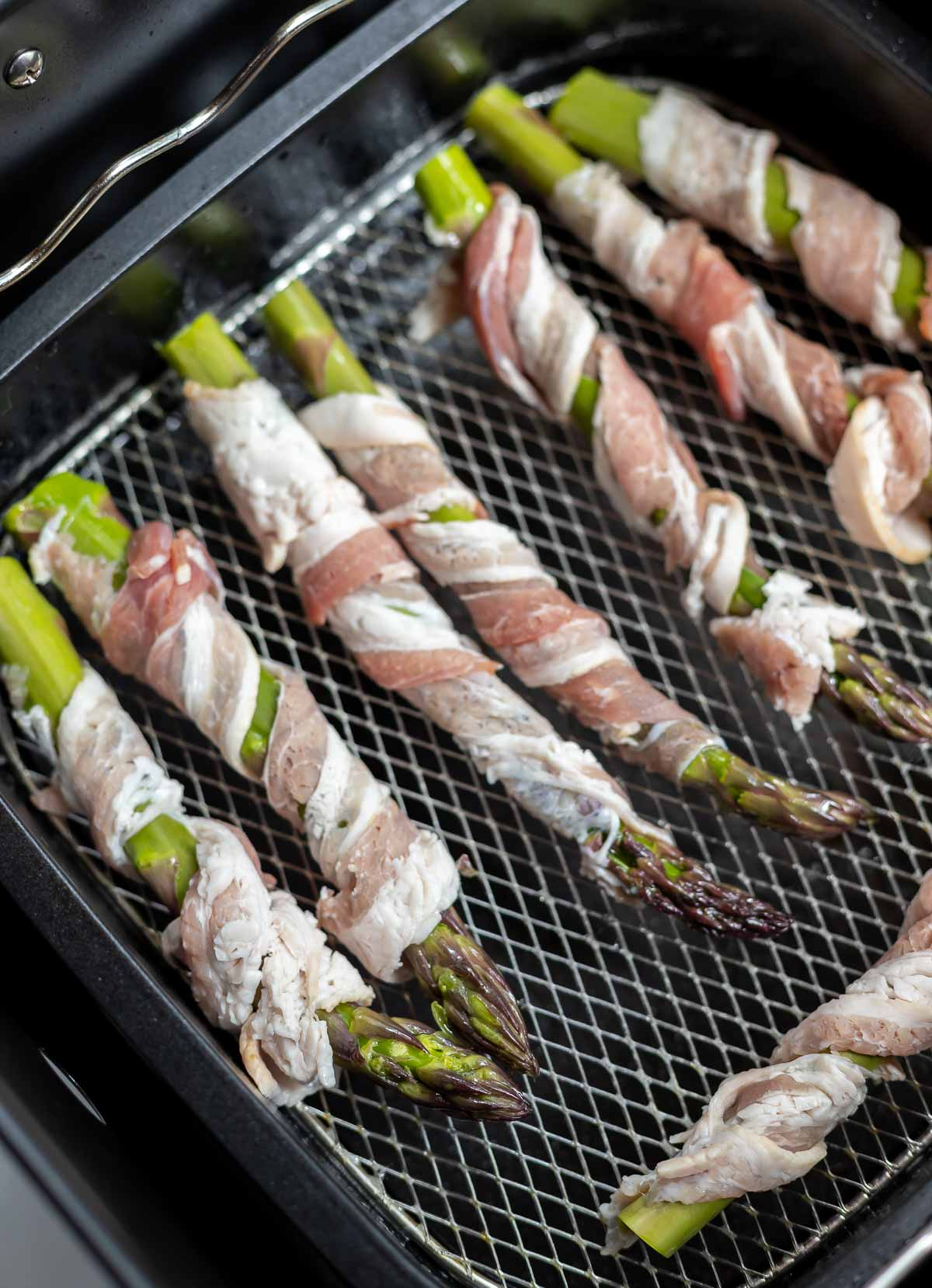 raw bacon wrapped asparagus in basket