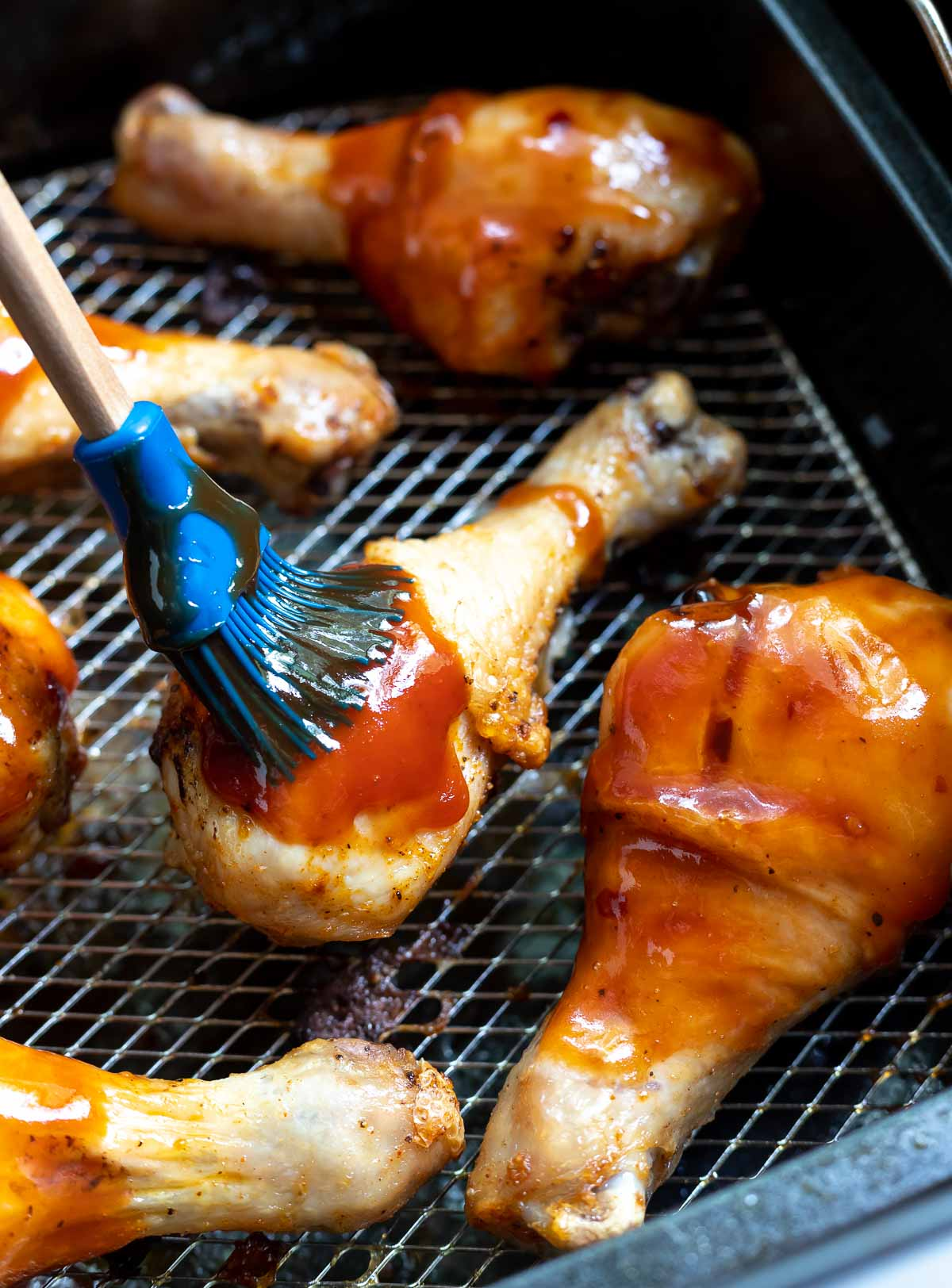 brushing bbq sauce onto chicken drumsticks