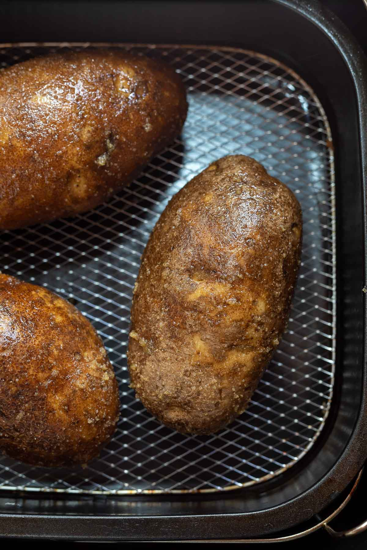 raw whole potatoes in air fryer basket