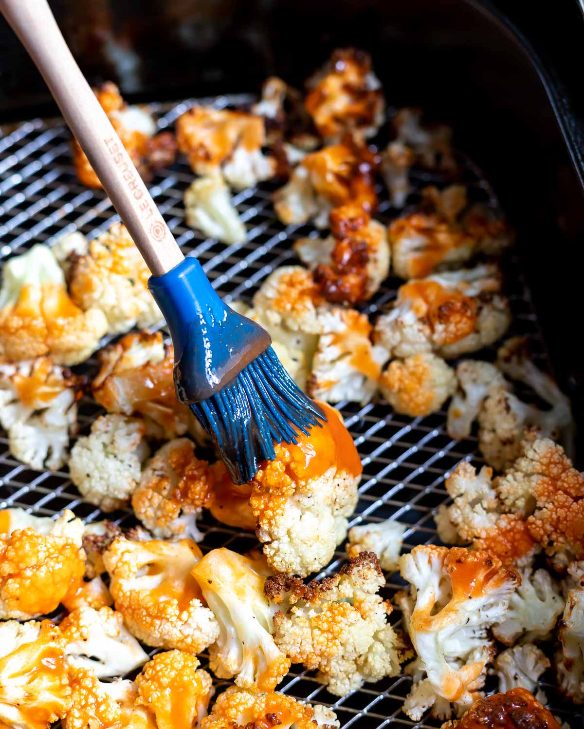 cauliflower in air fryer basket being brushed with buffalo sauce