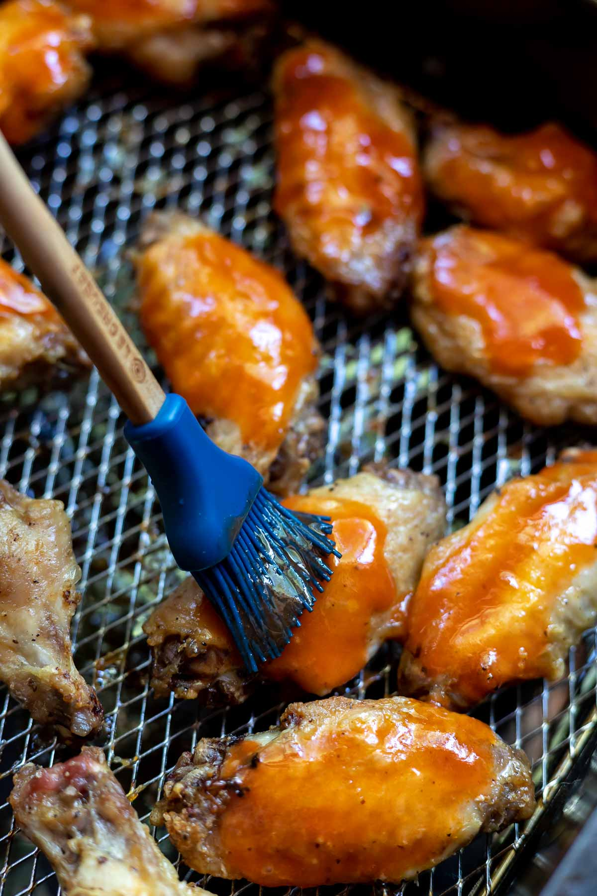 chicken wings being brushed with buffalo sauce in air fryer basket