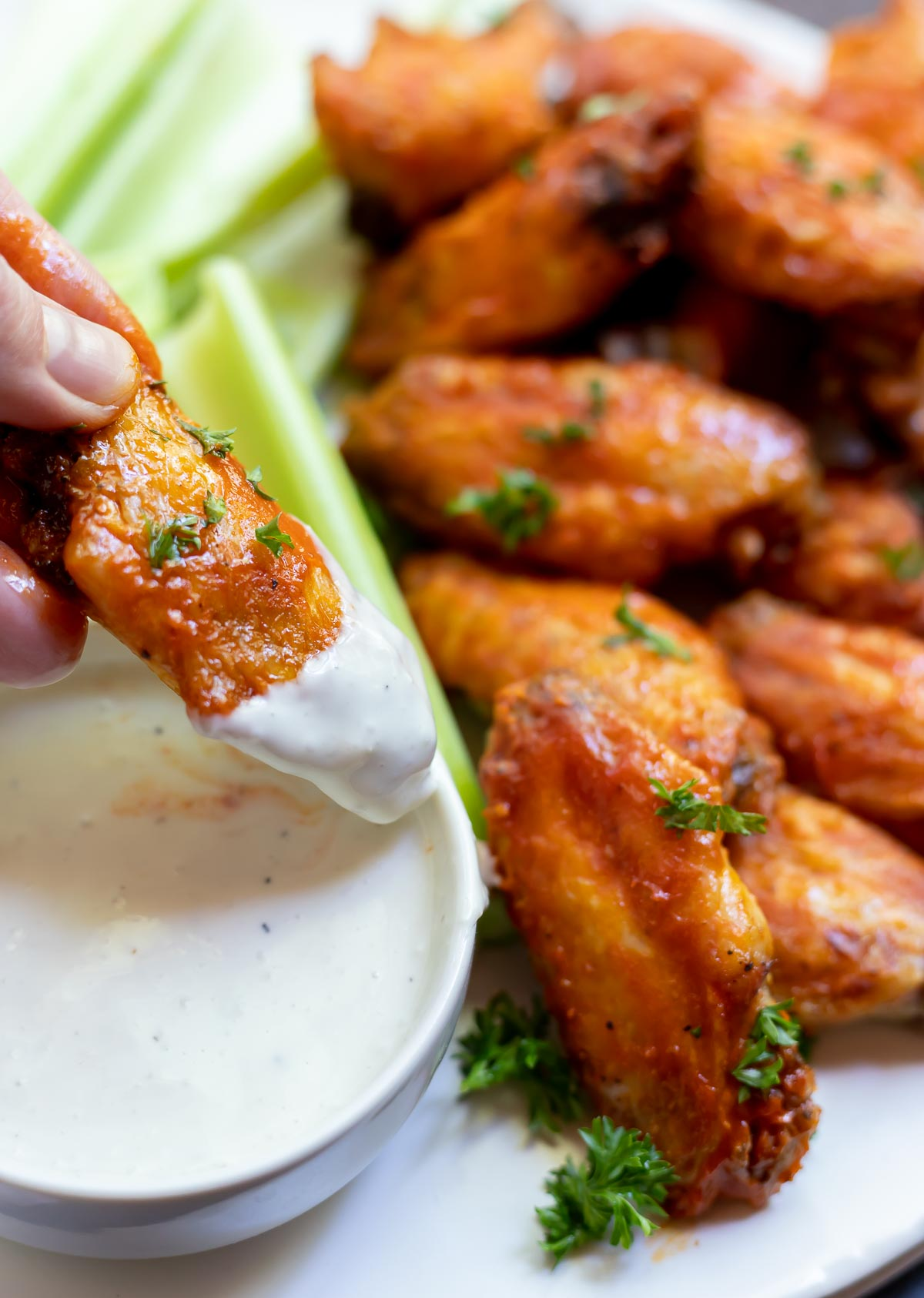 buffalo wing being dipped into blue cheese dip