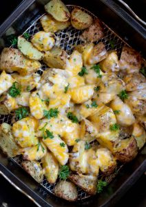 potatoes topped with melty cheese in air fryer basket