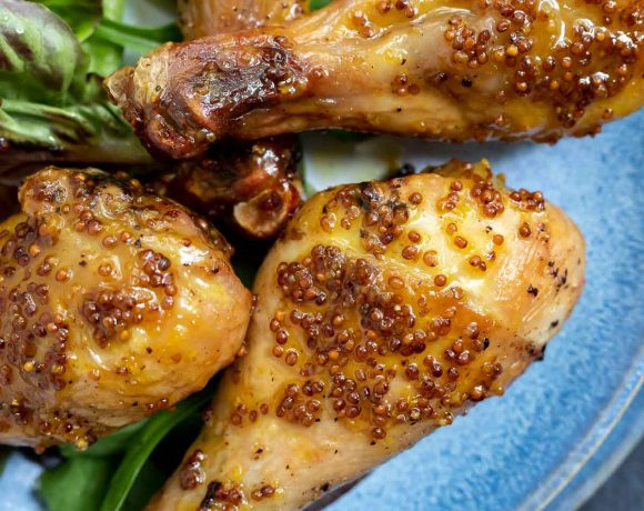 chicken legs coated in honey mustard sauce on a blue plate