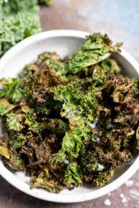green crispy kale chips in white bowl