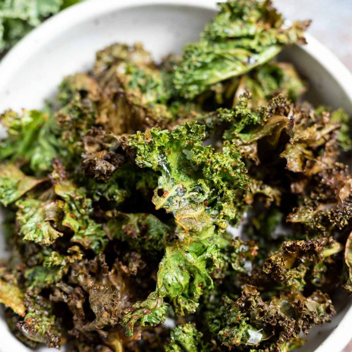 green crispy kale chips in white bowl
