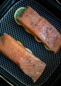 raw salmon fillets on top of sliced lemons in air fryer basket