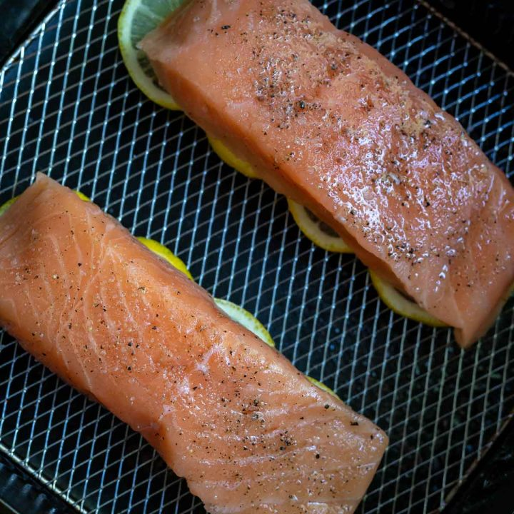 raw salmon fillets on top of sliced lemons in air fryer basket