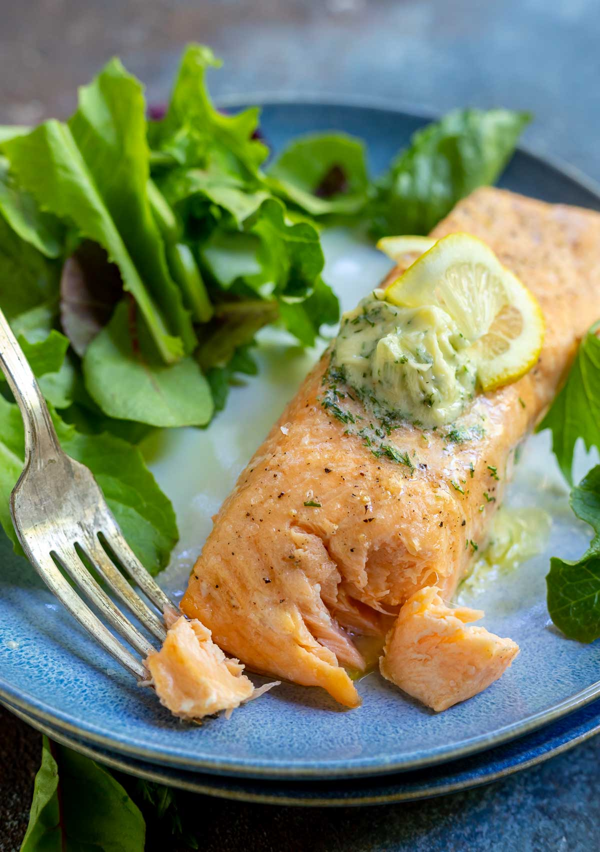 salmon fillet topped with butter and lemons on a blue plate