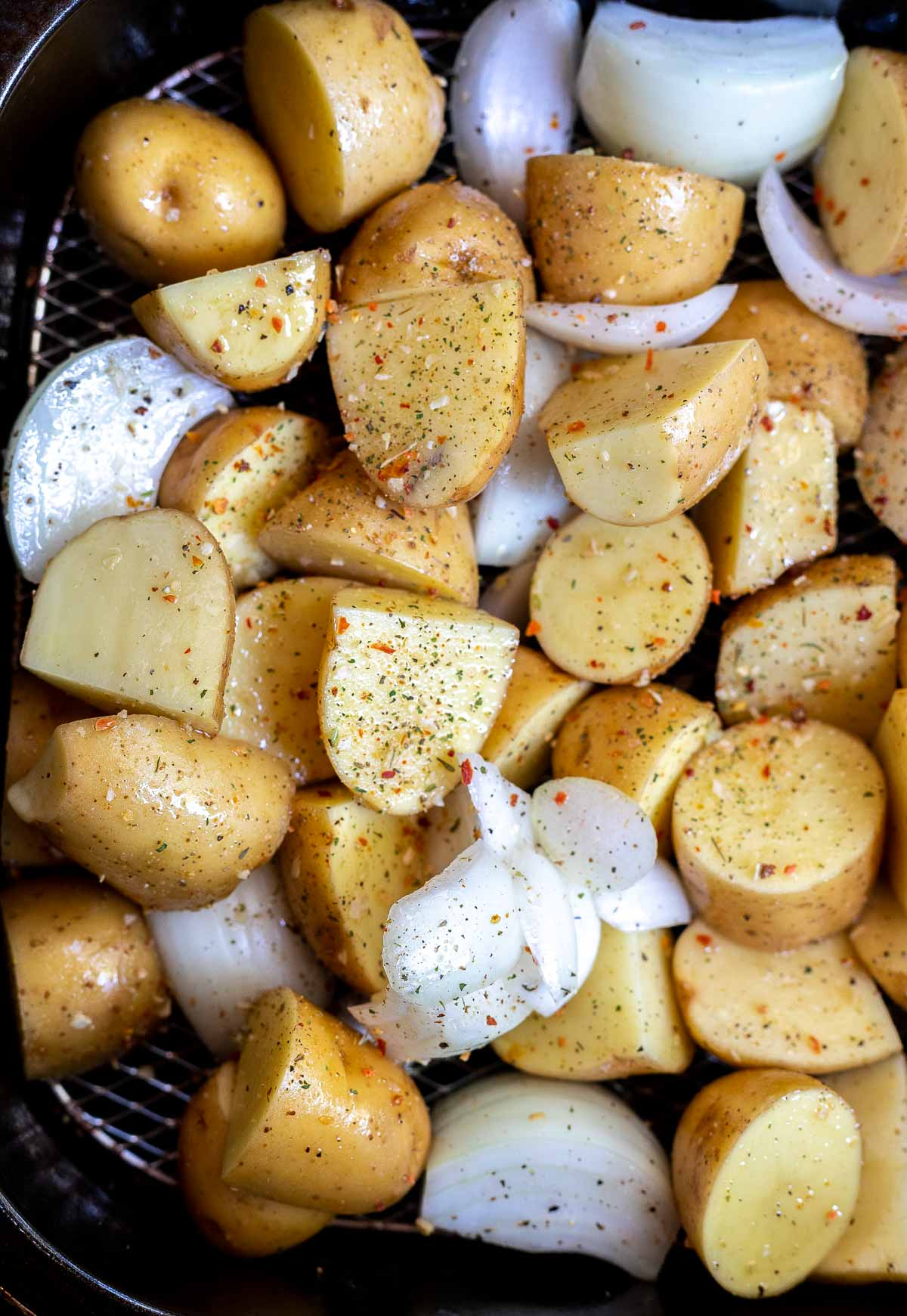 uncooked potatoes and onions in air fryer basket
