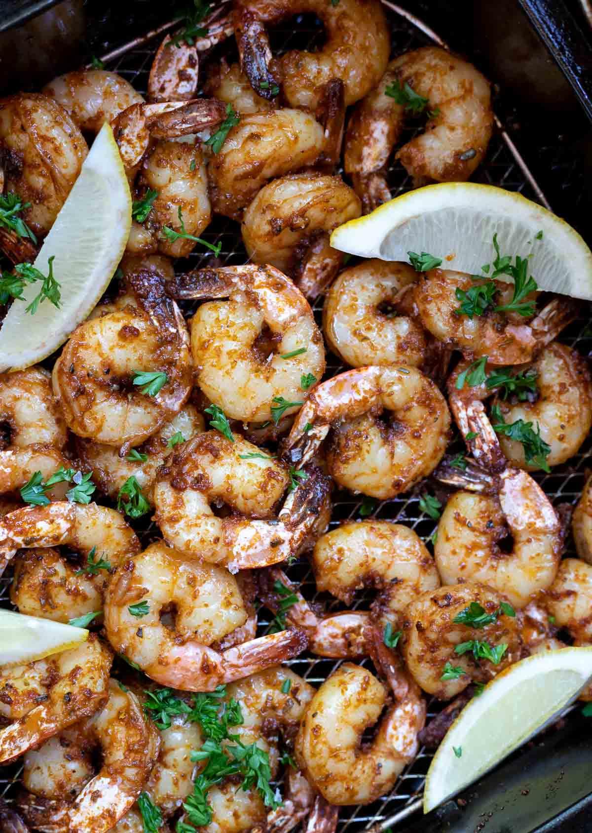 blackened shrimp and lemons in air fryer basket