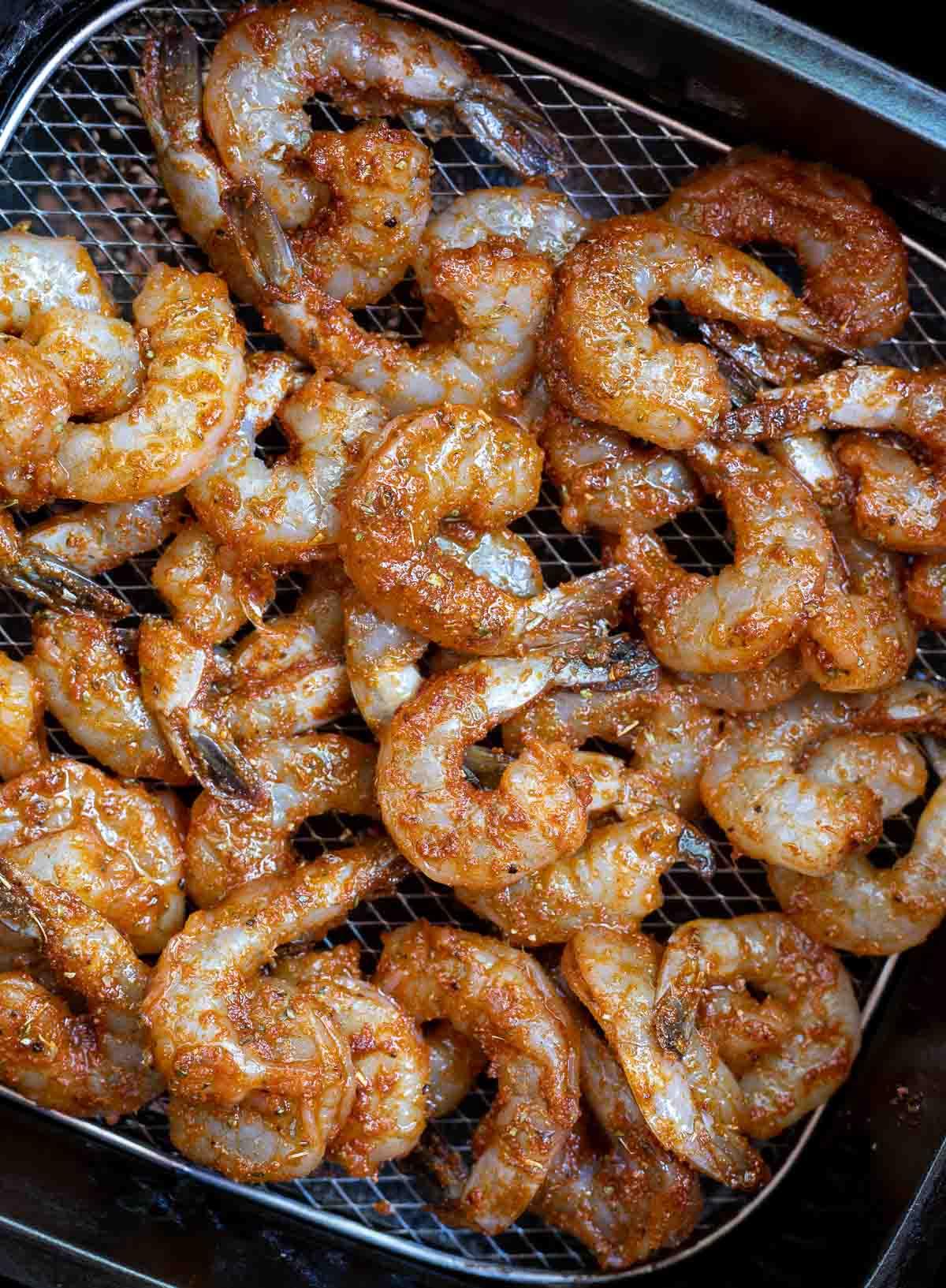 raw shrimp coated with blackened seasoning in air fryer basket