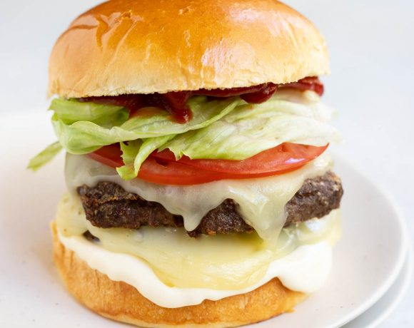 loaded cheeseburger on white plate