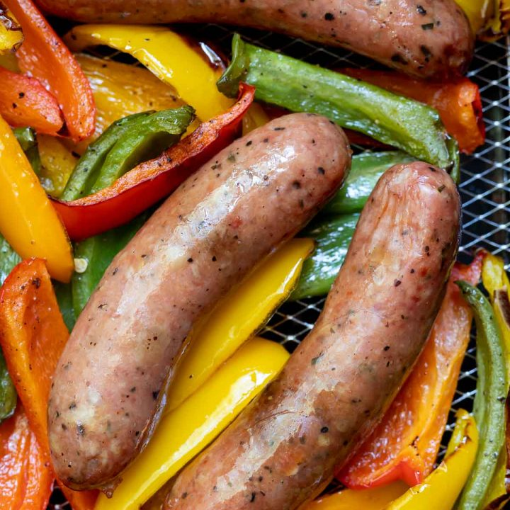 sausages and sliced peppers in air fryer basket