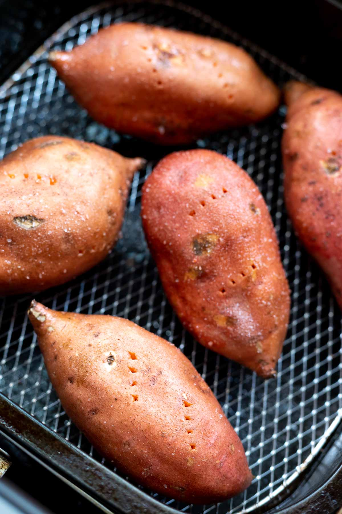 raw sweet potatoes in air fryer basket