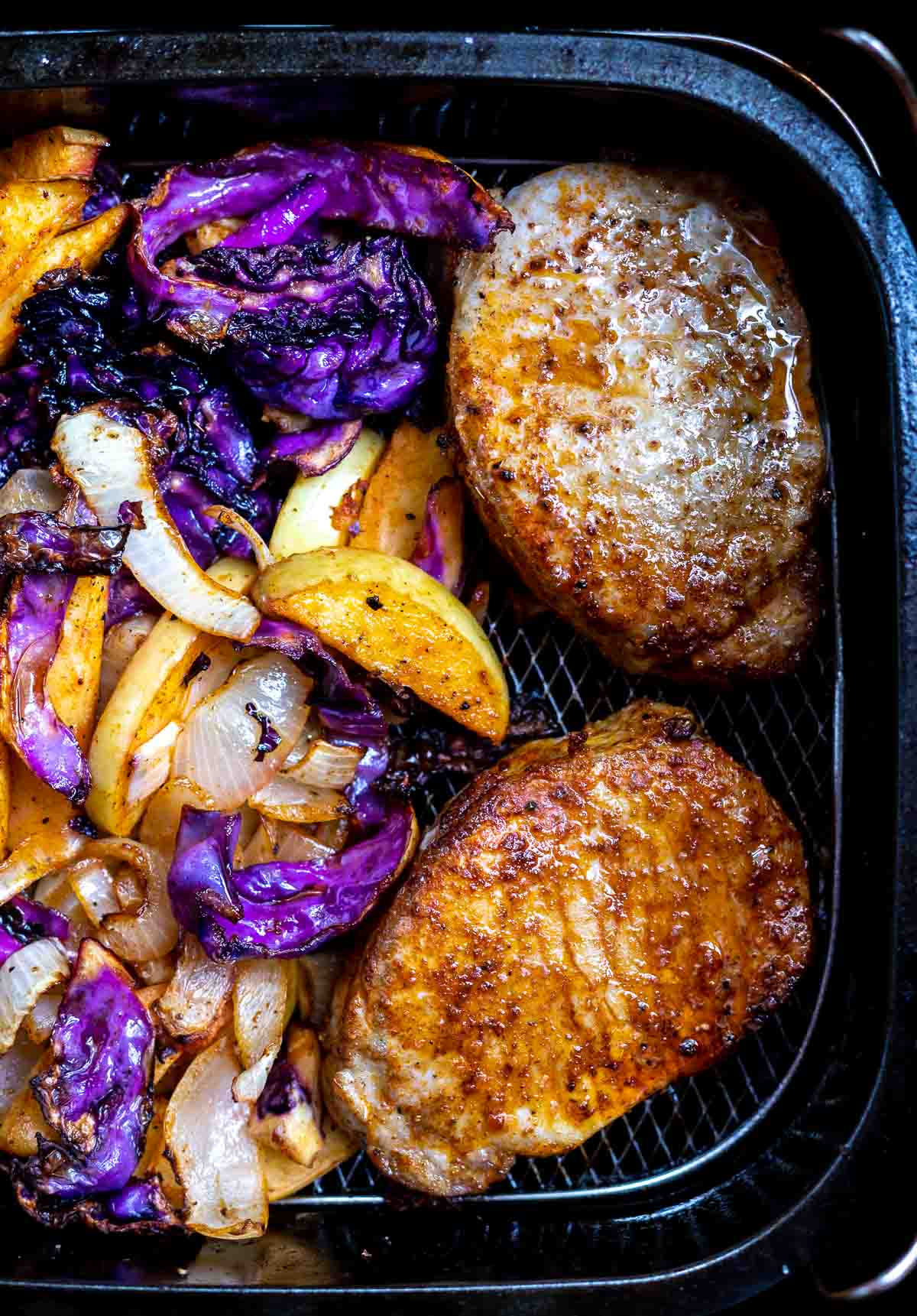 cooked pork chops, cabbage and apples in air fryer basket