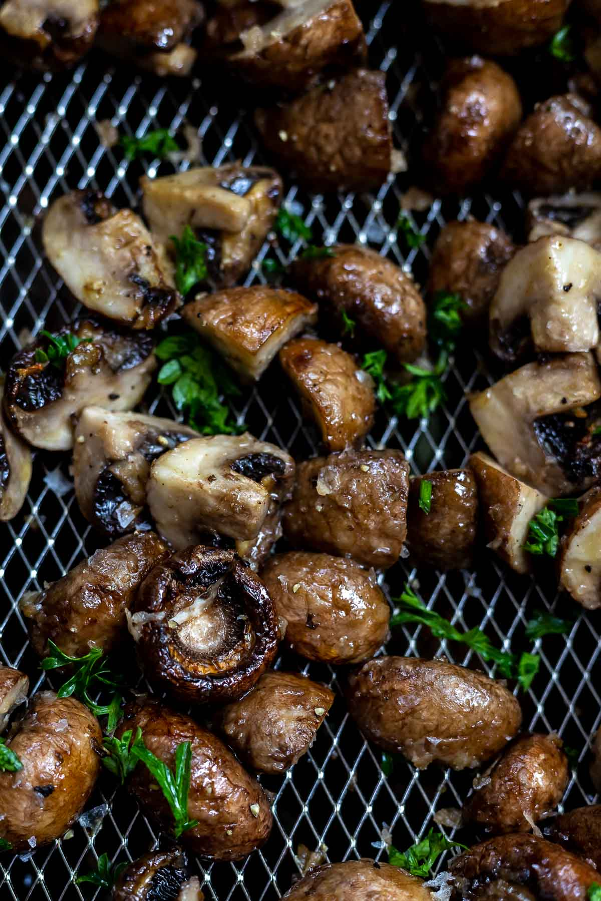 cooked mushrooms topped with parsley in air fryer basket