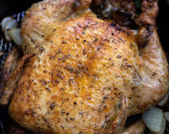 roasted chicken with golden brown skin in air fryer basket