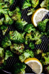 air fried broccoli in air fryer basket with lemon wedges