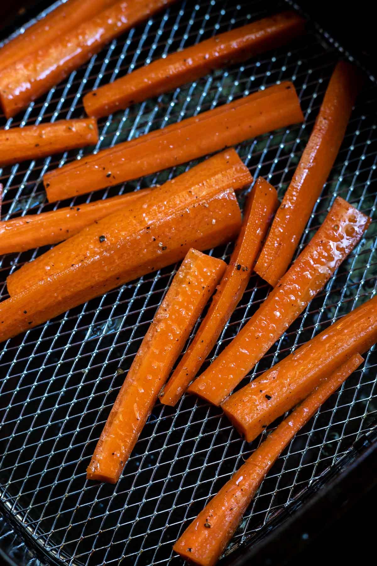 raw carrot sticks in air fryer basket