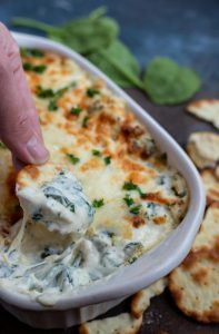 hand dipping cracker into hot spinach artichoke dip