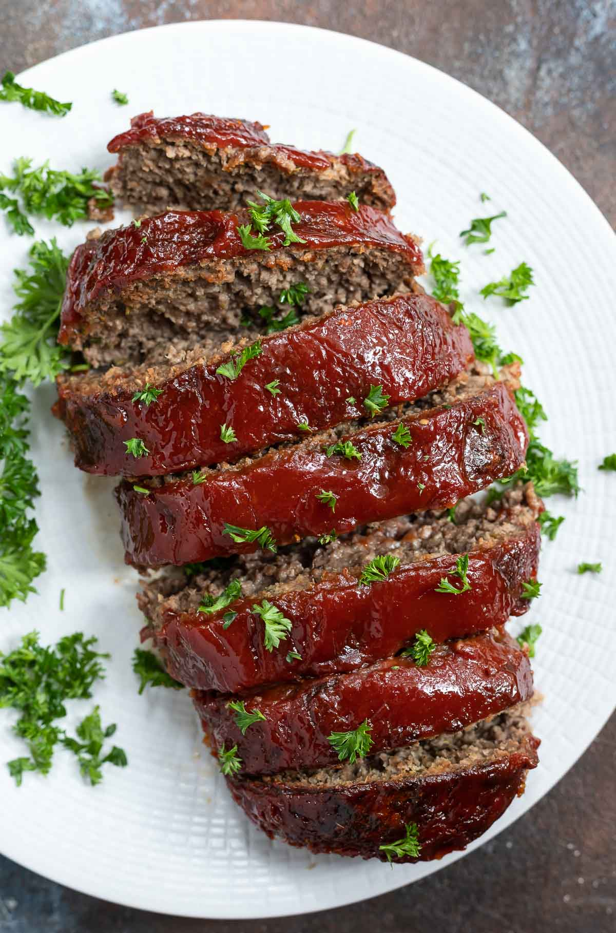 ketchup glazed meatloaf sliced and served on white plate
