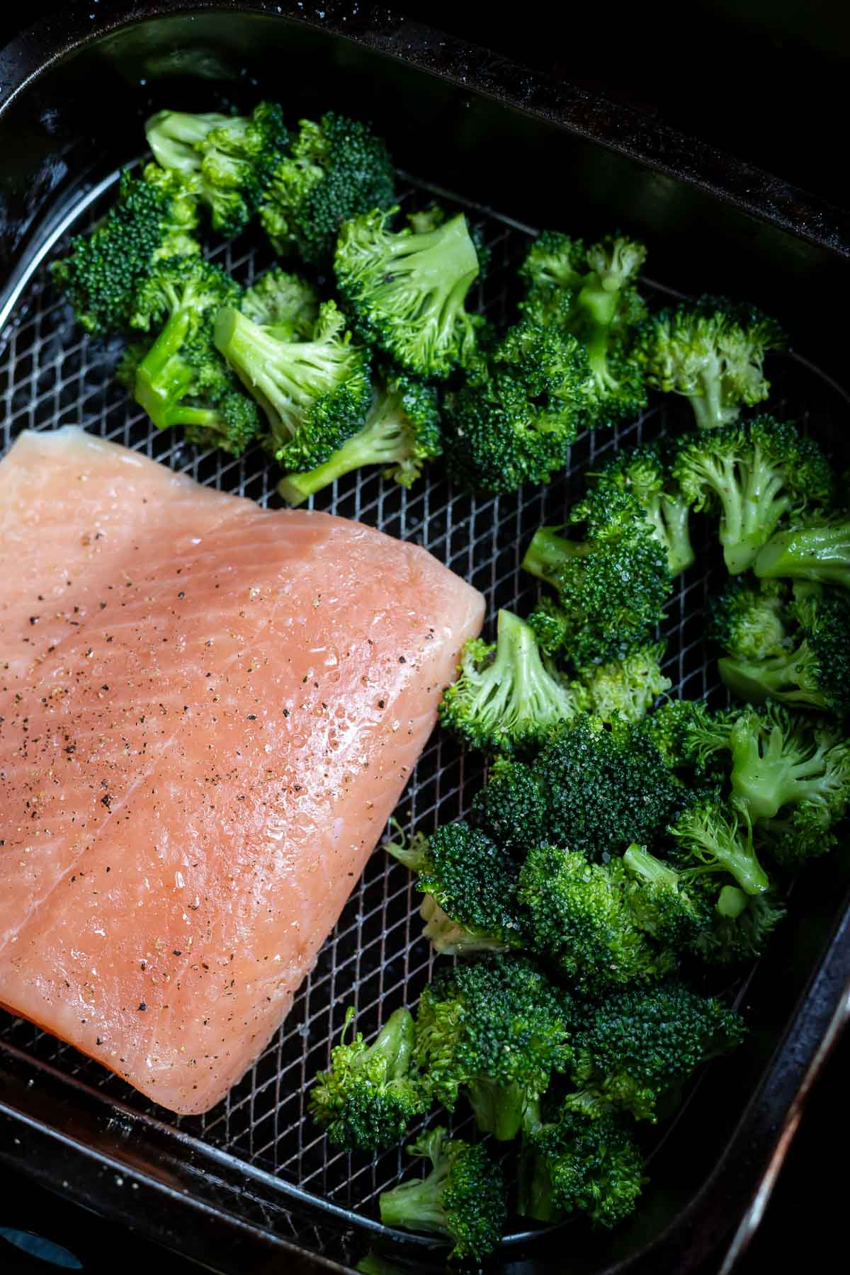raw broccoli and salmon in air fryer basket