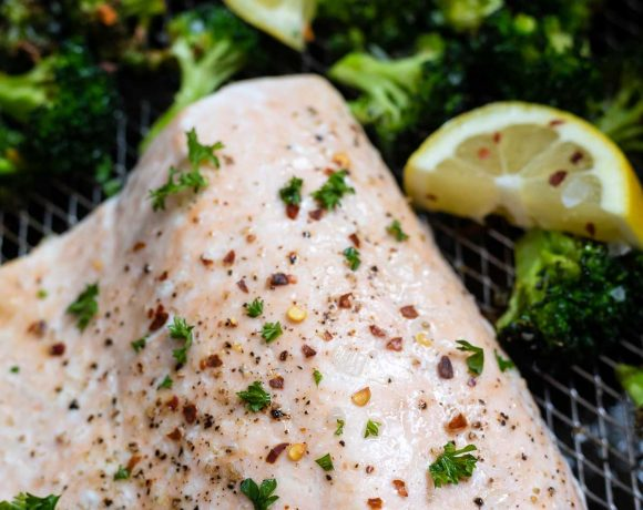 cooked salmon with broccoli and lemons in air fryer basket