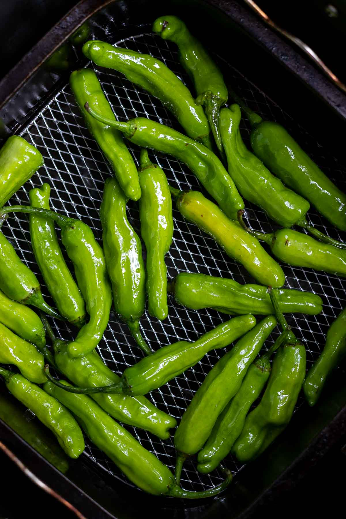 uncooked shishito peppers in air fryer basket