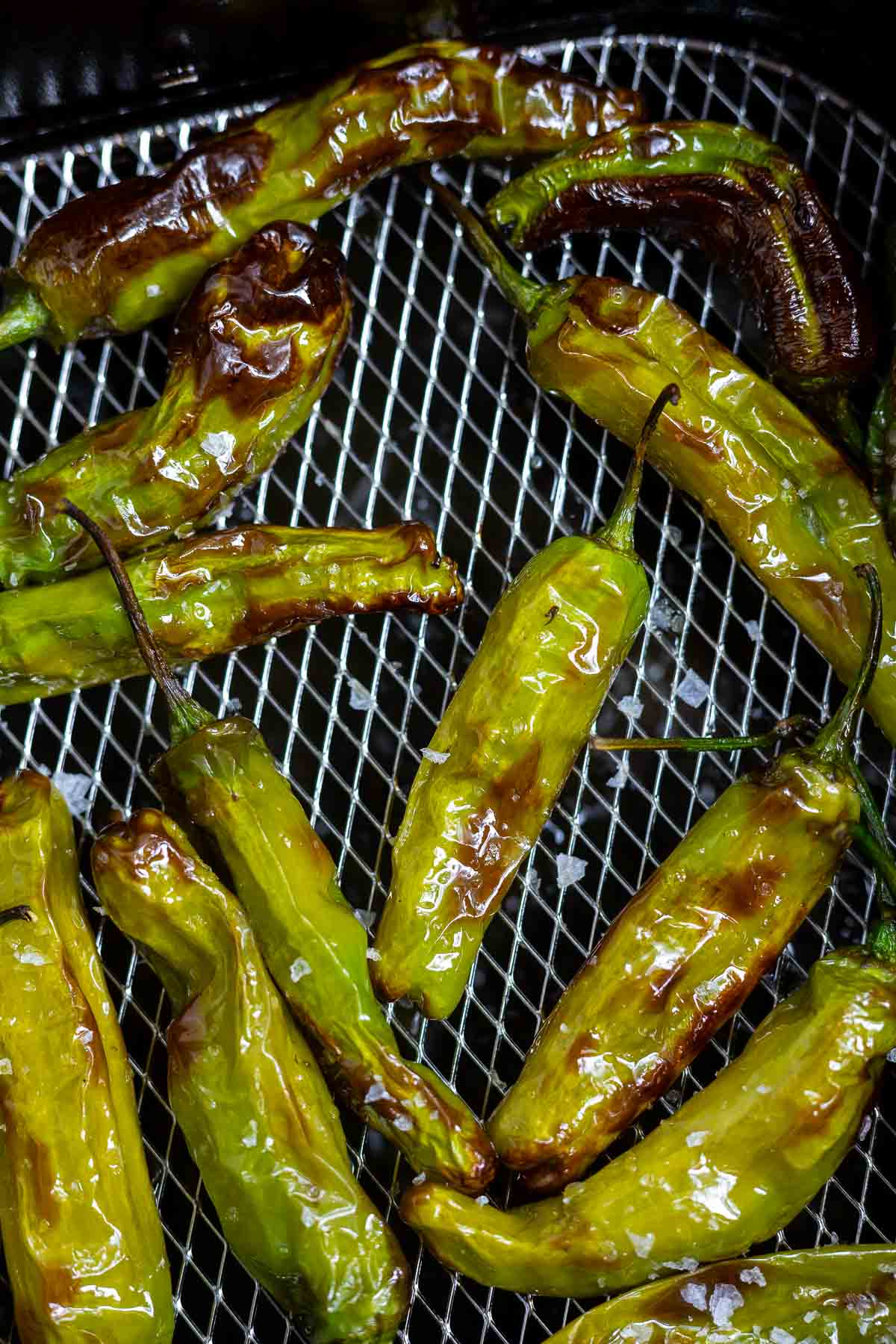 cooked shishito peppers in air fryer basket