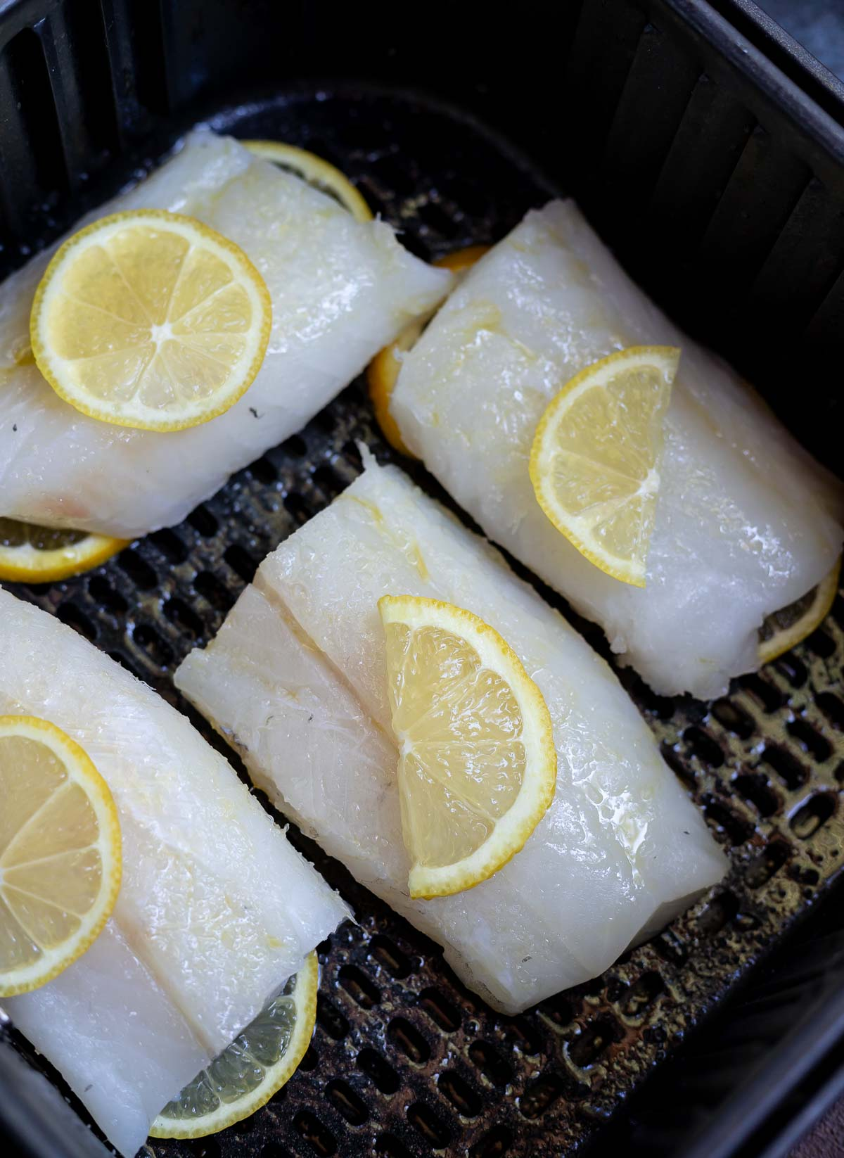 raw cod fish topped with lemon slices
