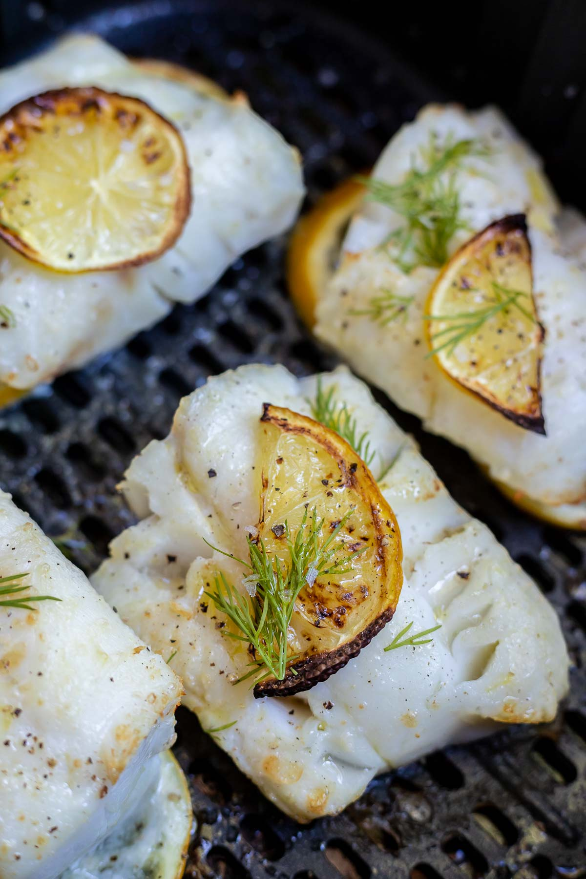cod topped with lemon slice and dill in air fryer basket