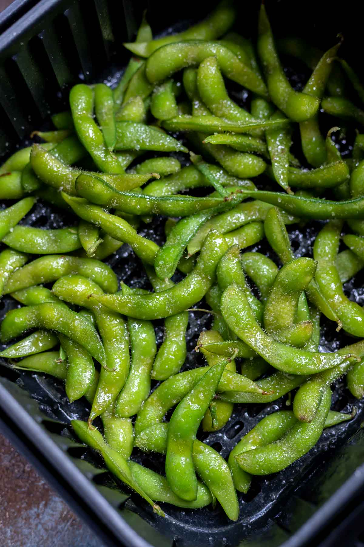 uncooked edamame in air fryer basket