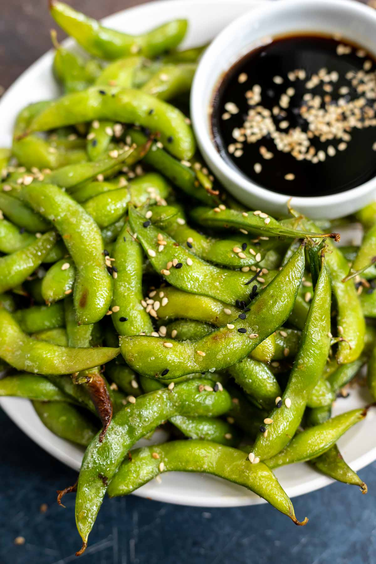 edamame topped with sesame seeds served on white plate with soy sauce