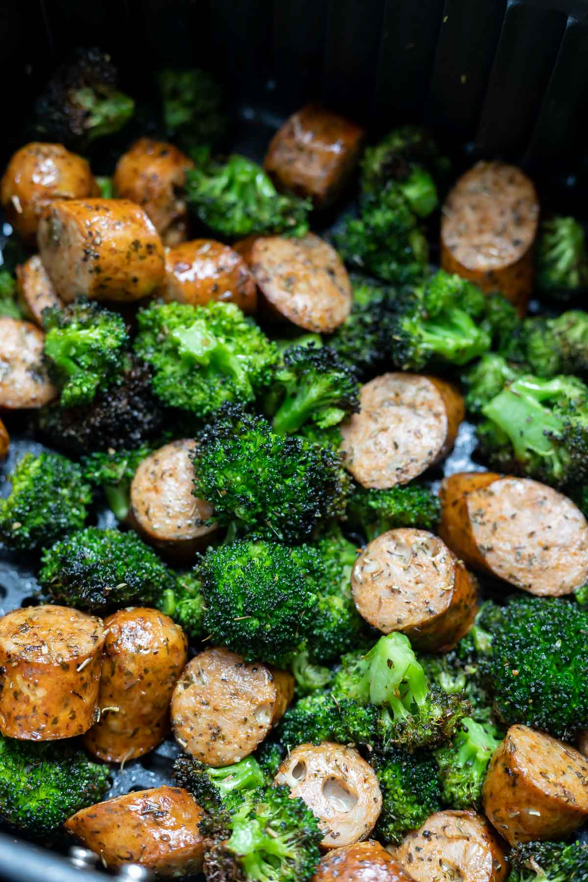 fresh green broccoli and sliced sausage in air fryer basket