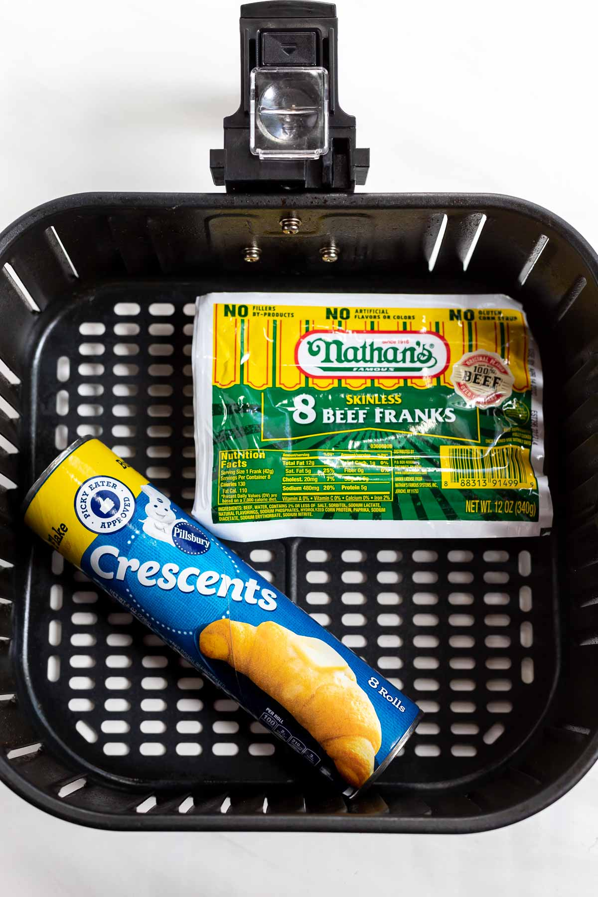 pack of hot dogs and crescent roll tube in air fryer basket