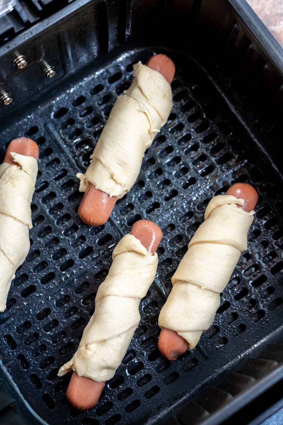 uncooked crescent dogs in air fryer basket