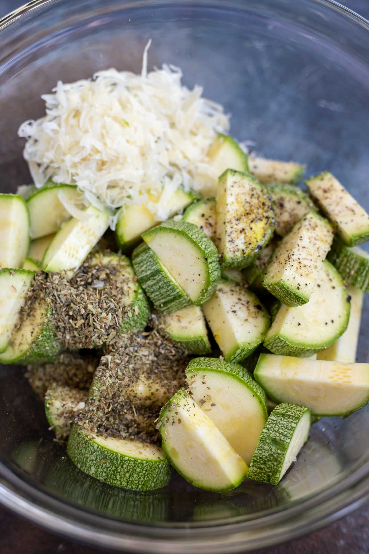 clear glass bowl filled with zucchini wedges, parmesan and Italian seasoning