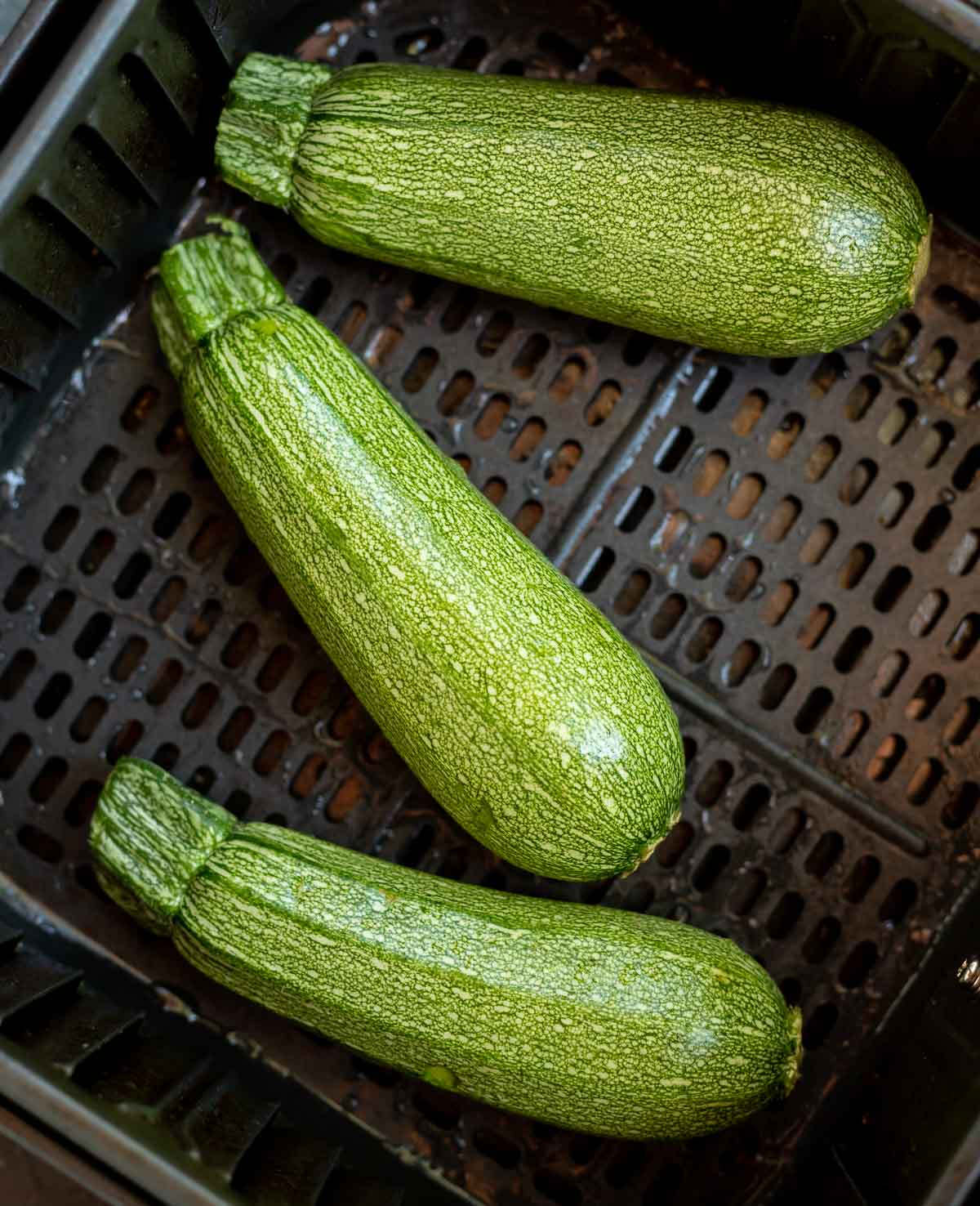 three green zucchinis in air fryer basket