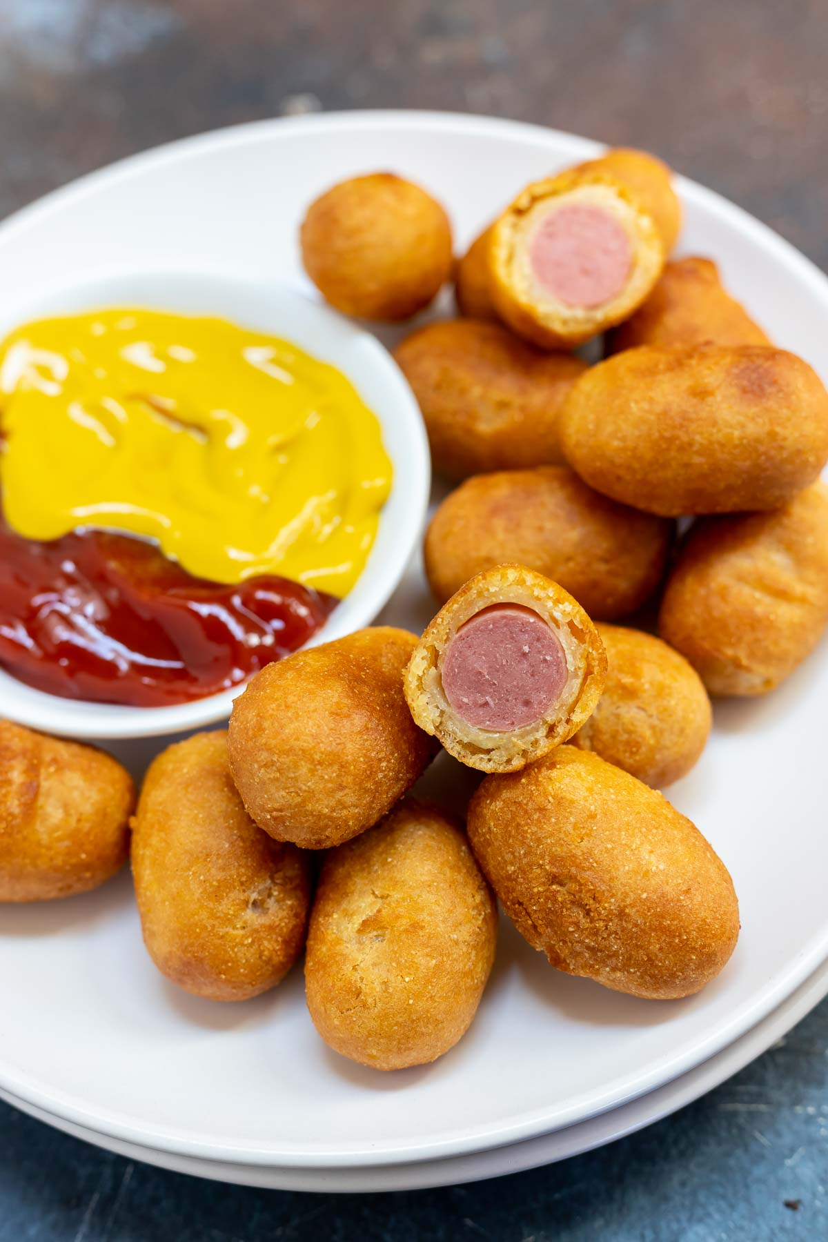 mini corndogs on white plate with dish of ketchup and mustard