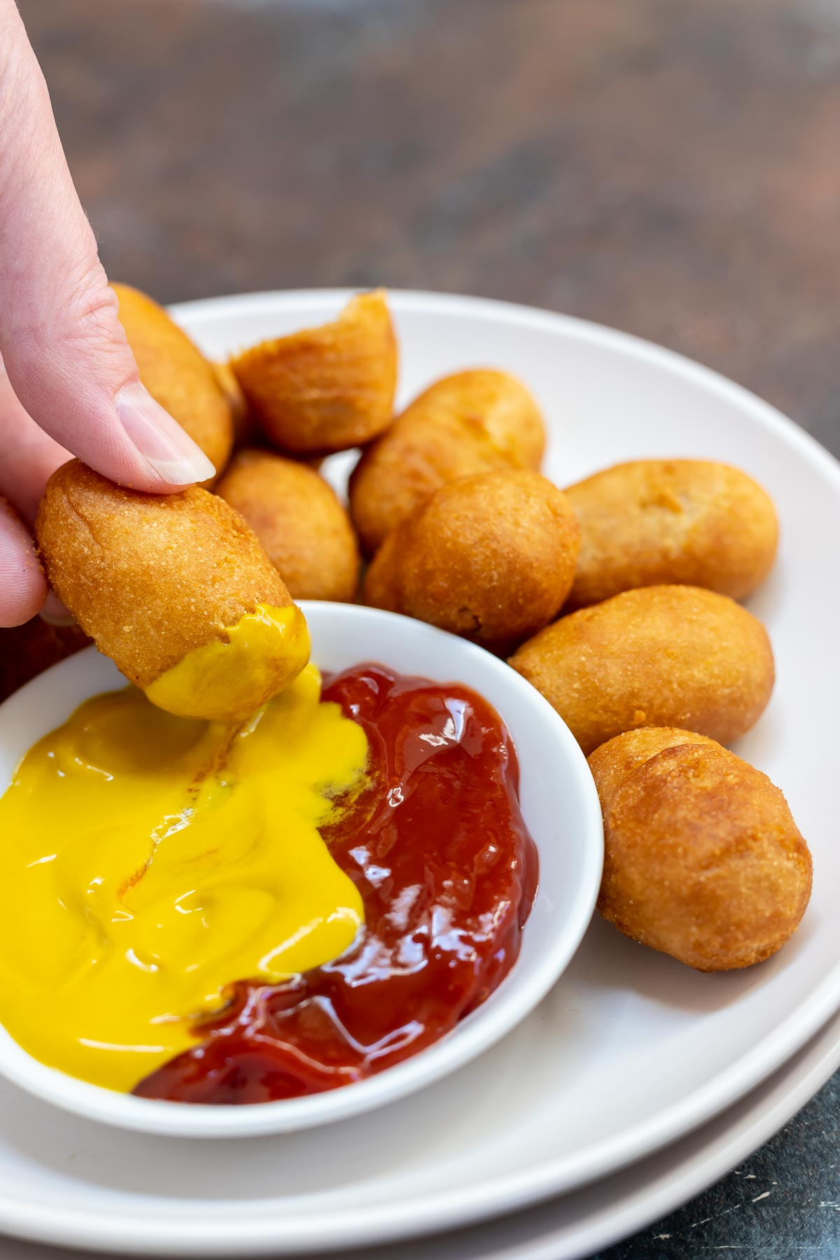hand dipping mini corndog into mustard