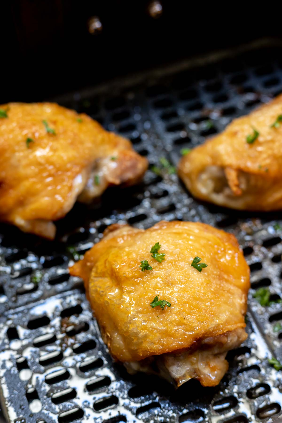 cooked golden skin chicken thighs in air fryer basket
