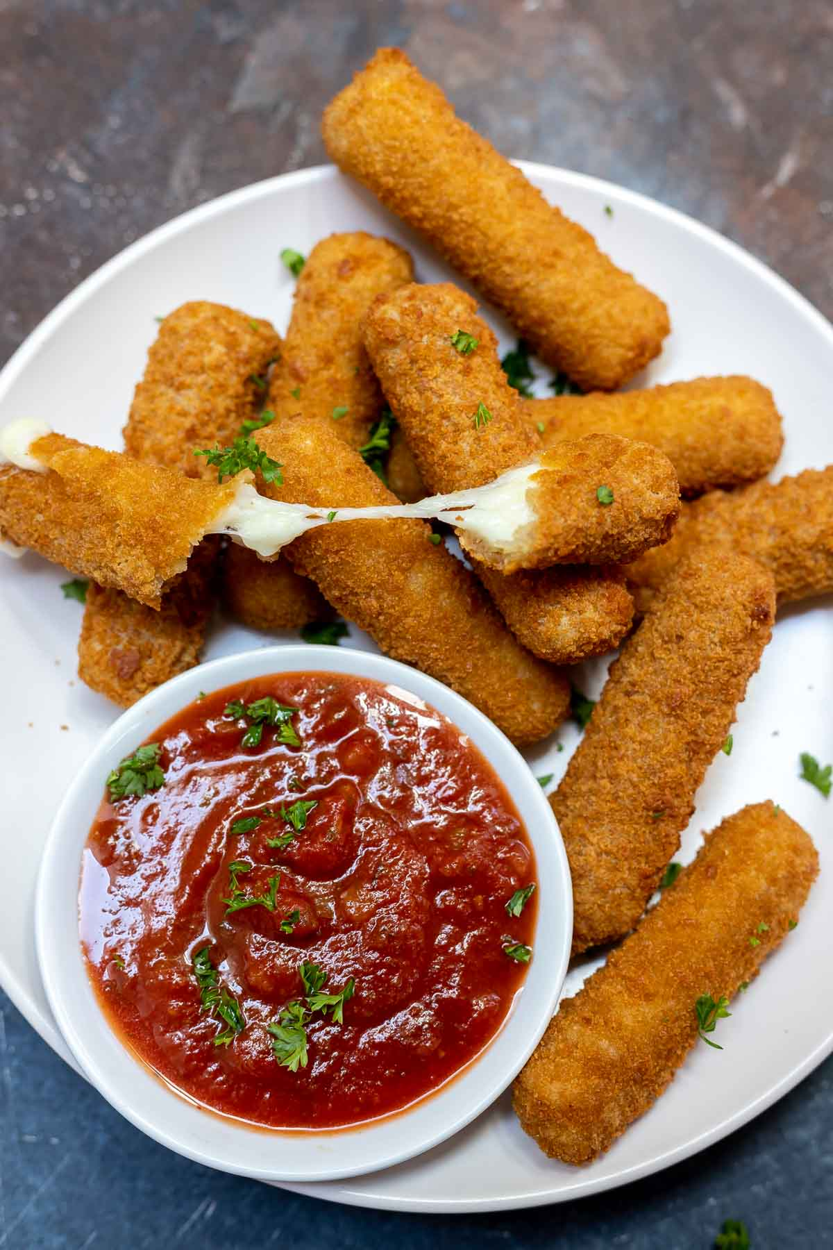 cooked mozzarella sticks on white plate with white bowl of red sauce